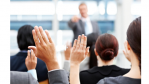 A picture of a group of people at a seminar, raising their hands