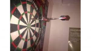 a picture of someone Aiming pass the dart board