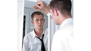 a real life picture of a white man looking in the mirror