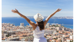 A real picture of a lady standing from the back with her arms up, facing the city from above