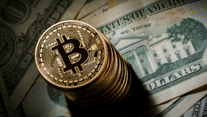 A picture of a day k of bitcoin on top of a twenty dollar bill